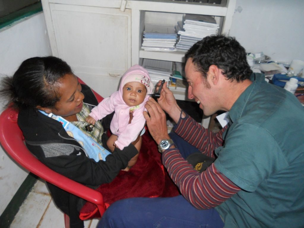 Volunteer Damien Rake with a young patient and mother at the community clinic Hatubuilico.