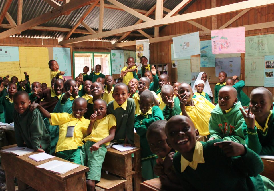 Children smiling in their classroom at Ruben Centre