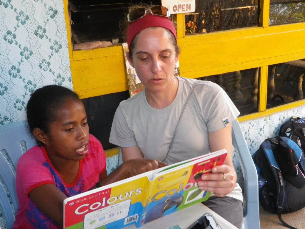 Volunteer reading a book to a child in Timor-Leste