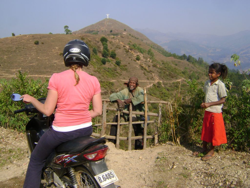 Woman on motorbike chatting with locals in Timor-Leste