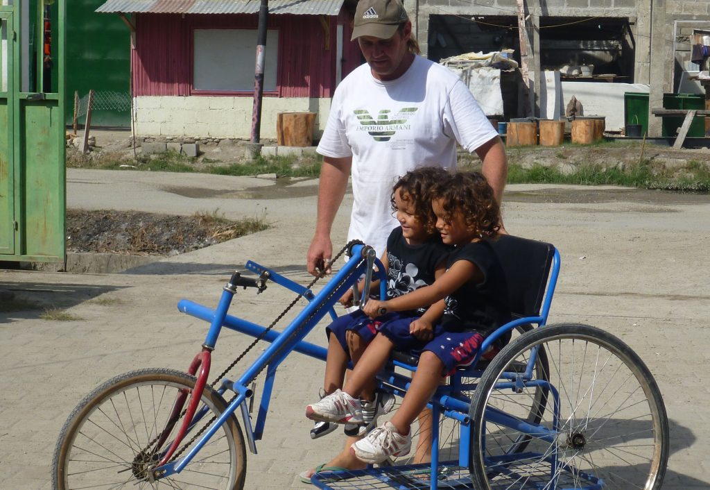 Barry Hinton and his two young sons riding a bike in Timor-Leste