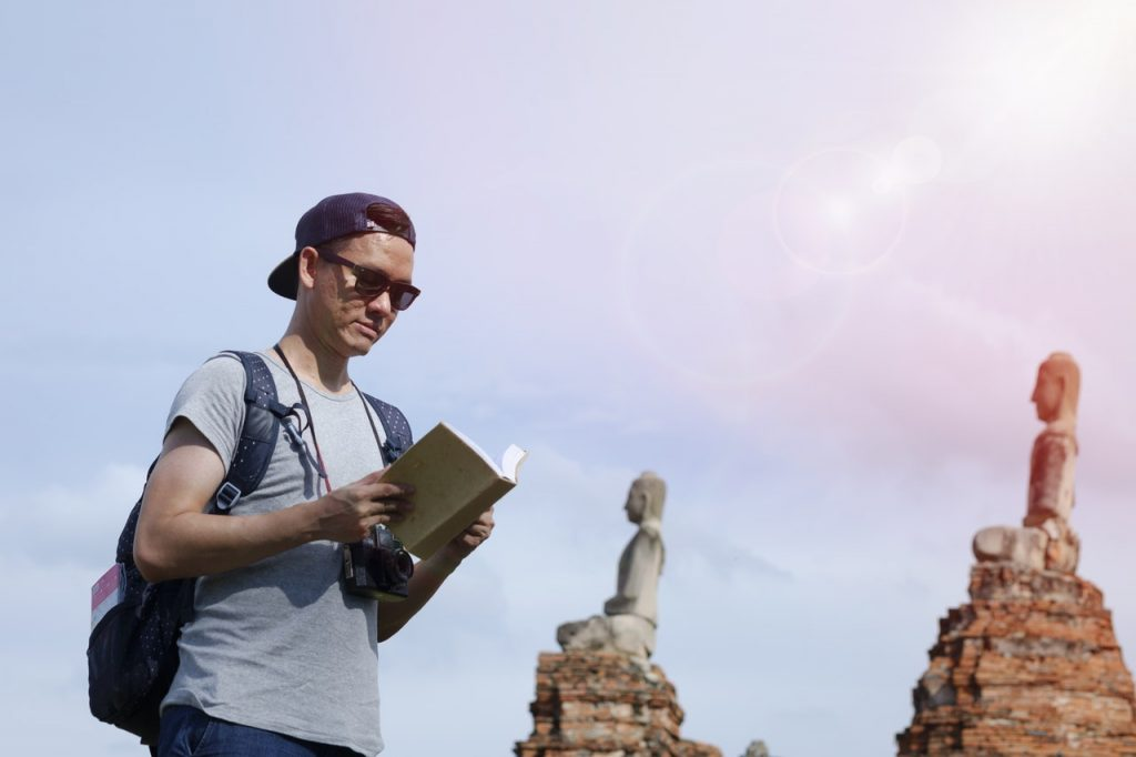 Young man with camera and guidebook