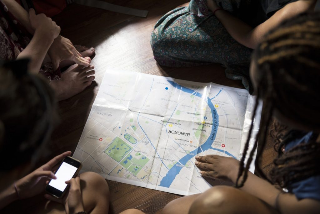 Travellers leaning over a map of Bangkok